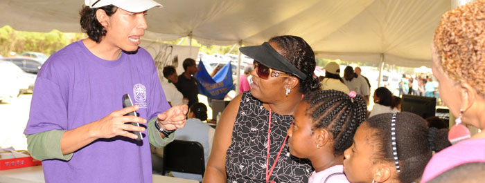 Student explains UVI programs at Afternoon on the Green.