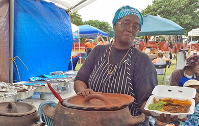 A Participant dishes Food at the annual Agriculture and Food Fair on St. Croix