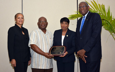 School of Education Professors Dr. Nancy Morgan,  Dr. Dennis Griffith and Dean Dr. Linda Thomas accept presidential award from UVI President Dr. David Hall.
