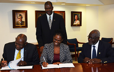 UVI President David Hall and Dr. Donna Powell Wilson, Council of Community Colleges of Jamaica executive director, sign a memorandum of understanding in the Administration and Conference Center on the St. Thomas Campus, while Dr. Haldane Davies, vice president for Business Development and Innovation, and Quince Francis, board chairman for the CCCJ look on.