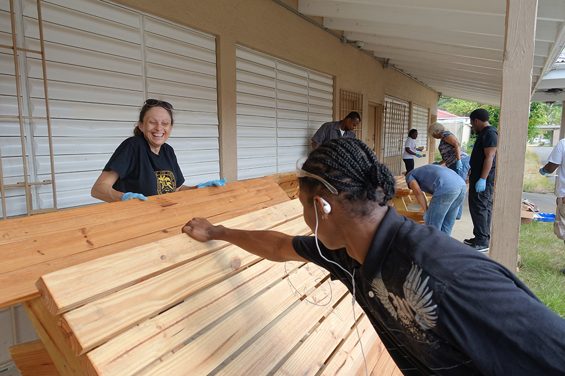 Volunteers paint benches at Addelita Cancryn School.