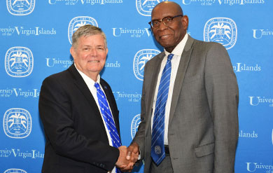 UVI Board Chairman Henry Smocks congratulates UVI President David Hall