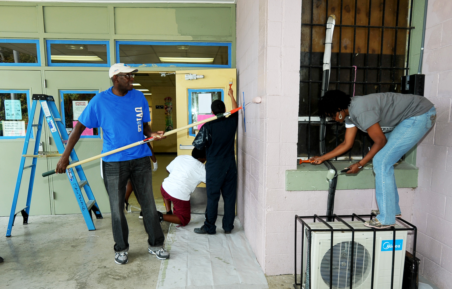 UVI President David Hall and other UVI volunteers paint the Alexander Henderson Elementary School.